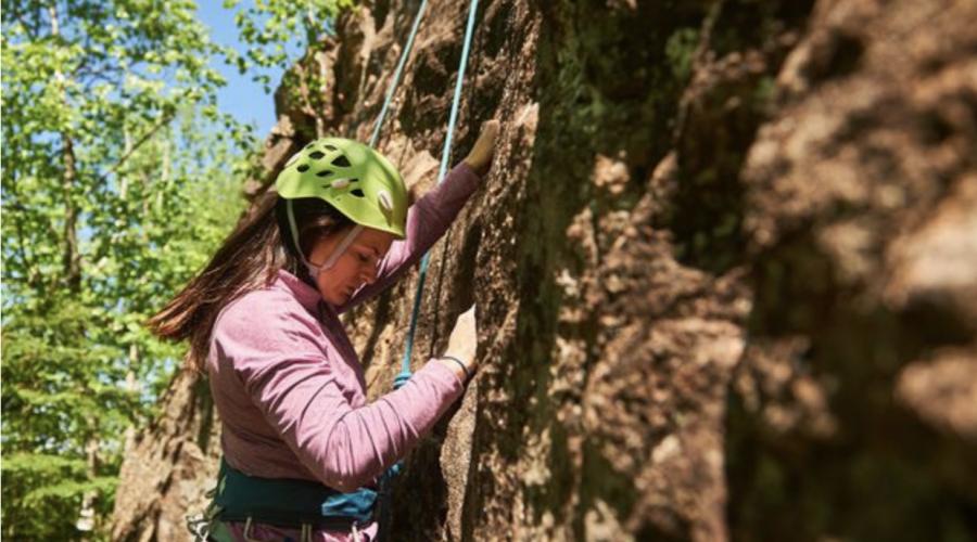 A woman climbing up a cliff