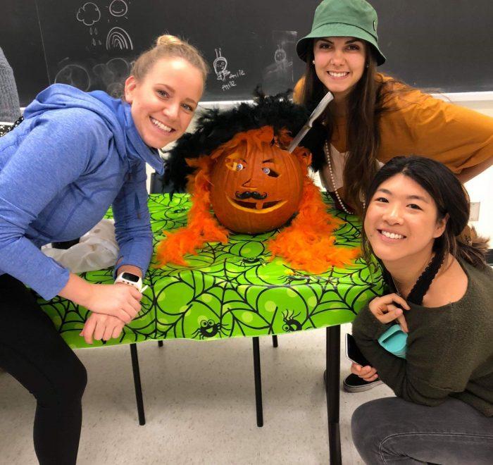 Three women sit around a pumpkin